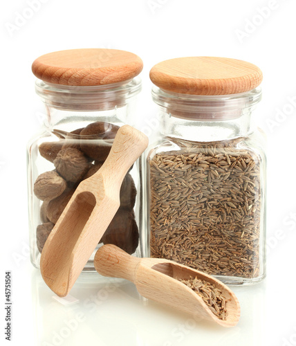 Tuinposter Kruiden 2 jars and wooden spoons with nutmeg and cumin isolated on white