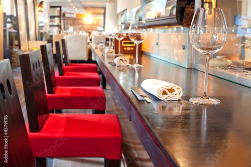 czerwone-krzesla-w-poblizu-baru-w-okularach-recznik-w-restauracji-sushi