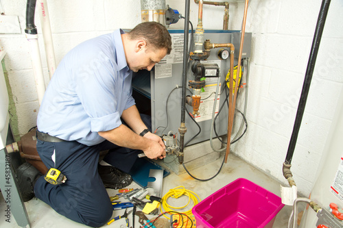 Fototapeta Plumber repairs furnace obraz