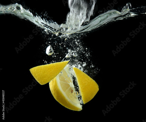 Spoed Foto op Canvas Opspattend water Sliced lemon in the water on black background