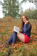 Young beautiful girl with red hair reading a book