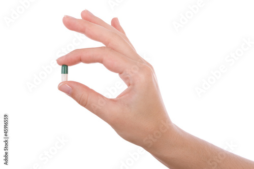 Obraz Hand holding a capsule or pill isolated on white - fototapety do salonu