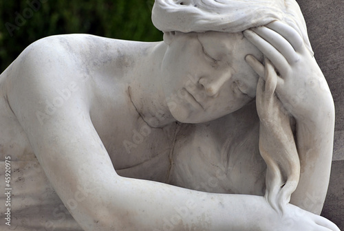 Foto op Canvas Begraafplaats statue of a sad woman in cemetery