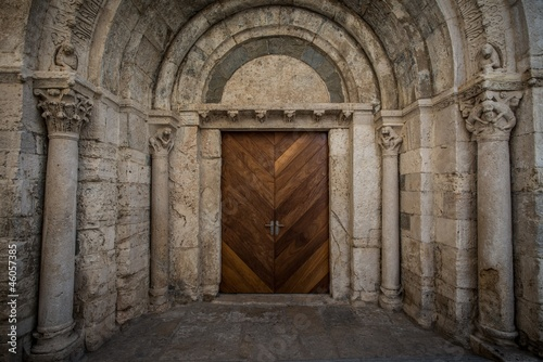 Wooden door in ancient archway Fototapeta