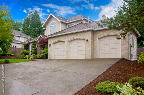 Fotografía  Large beige house with three car garage and large driveway.