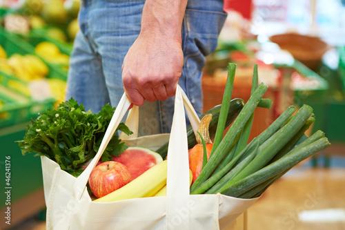 Fotografía  Mann mit Beutel im Supermarkt
