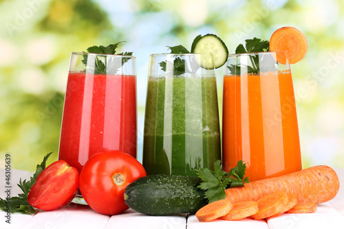 Fresh vegetable juices on wooden table, on green background - 46305639