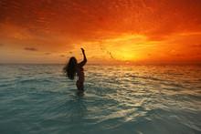 Woman Splashing In Sea On Sunset