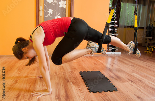 Fotografía  Beautiful girl exercising in the gym with suspension device