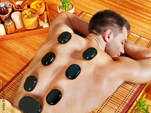 Akustikstoff - Man getting stone therapy massage .
