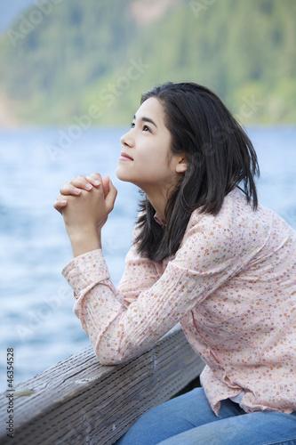 Fotografie, Obraz  Young teen girl sitting quietly on lake pier, praying