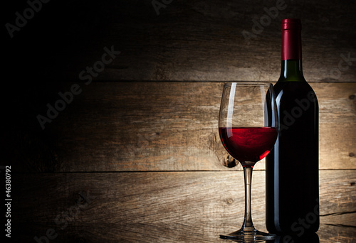Fotografia  Wine glass and Bottle on a wooden background