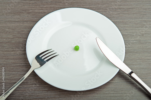Fotografía  diet concept. one pea on an empty white plate