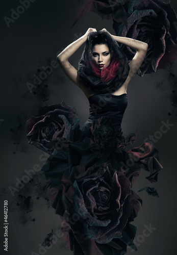 Fotografering  mysterious woman in dark hood and rose dress