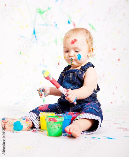 kleines junges baby malt mit Farben und pinsel Canvas Print