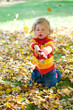 child is playing in autumn foliage