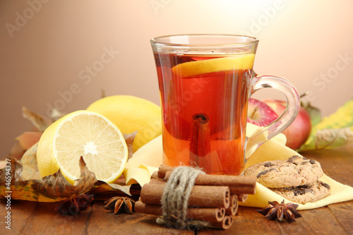Staande foto Thee cup of hot tea and autumn leaves, on brown background