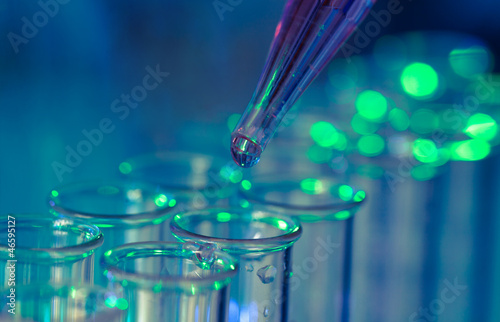 Pipette adding fluid to one of several test tubes Wallpaper Mural