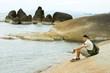 The man sitting on the sea coast