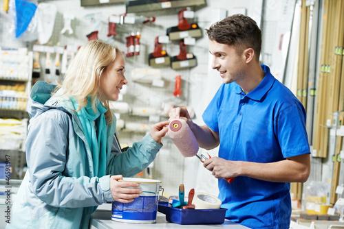 Stampa su Tela Seller demonstrating paint roller to buyer