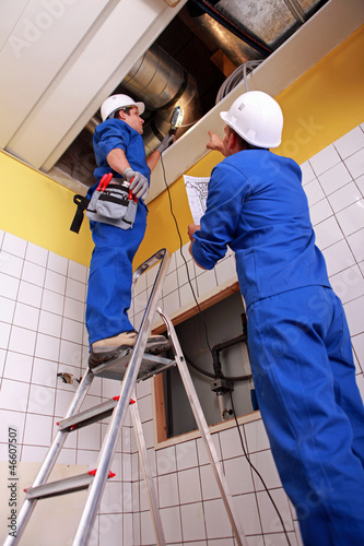 Fotografija  Man and woman repairing ventilation system