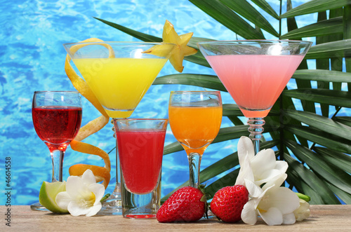 exotic cocktails and flowers on table on blue sea background - 46614558