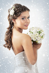 Naklejka A young woman in a bridal dress on a snowy background