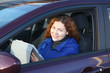Young woman with touchpad smiling in car on driver seat