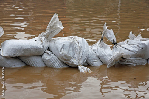 Fotografie, Obraz  sandbags for flood defense and brown water