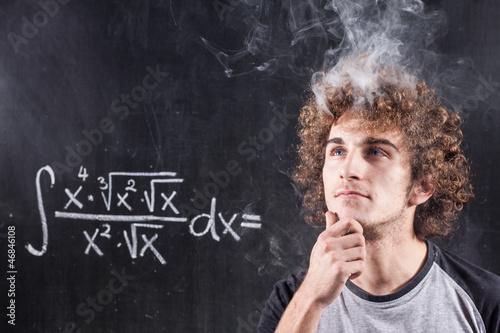 Fotografie, Obraz  Thinking boy solving equation with smoking head and blackboard