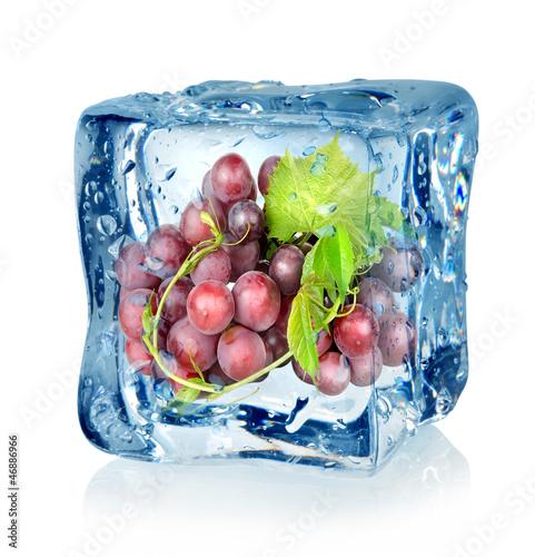Staande foto In het ijs Ice cube and blue grapes