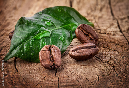Photo sur Toile Salle de cafe Coffee grains and green leaf on grunge wooden background