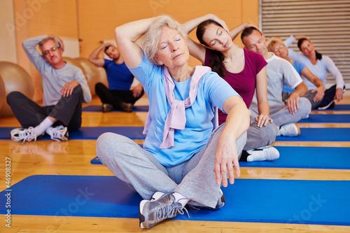 Staande foto School de yoga Gruppe beim Rückentraining im Fitnesscenter