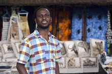 African Curio Salesman Vendor  In Front Of Ethnic Wildlife Items