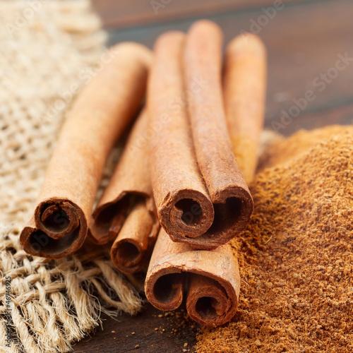 Fotografie, Obraz  Cinnamon sticks and  powder in wooden scoop