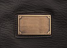 Metal Label On Old Black Leath...