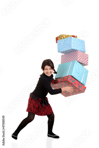 young girl dropping pile of christmas gifts