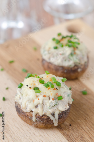 Stuffed mushrooms, baked with cheese and herbs on a wooden board