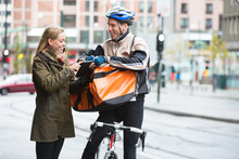 Courier Delivery Man Showing Digital Tablet To Young Woman