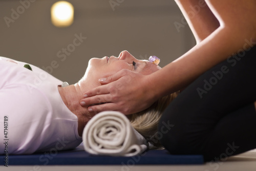 Photo  Young therapist arranging crystals on female client for reiki th