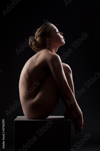 Beautiful nude woman sit in dark on cube