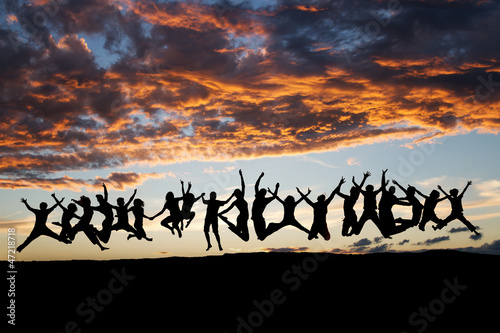 silhouetted large group of teens jumping after sunset