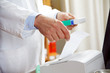 Hände, Medikament und Rechnung