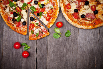 Obraz na Szkle Do baru Delicious italian pizzas served on wooden table