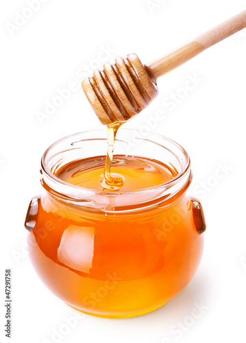 Valokuva  Glass jar of honey with wooden drizzler isolated on white