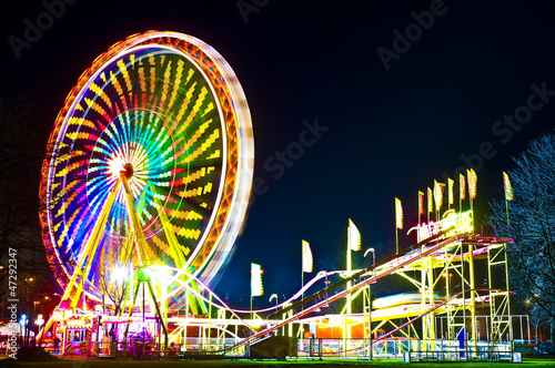 In de dag Amusementspark Amusement park at night - ferris wheel in motion