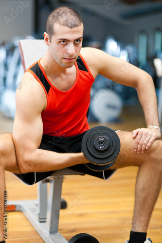 Spoed Foto op Canvas Fitness Young athlete lifting weights in the gym