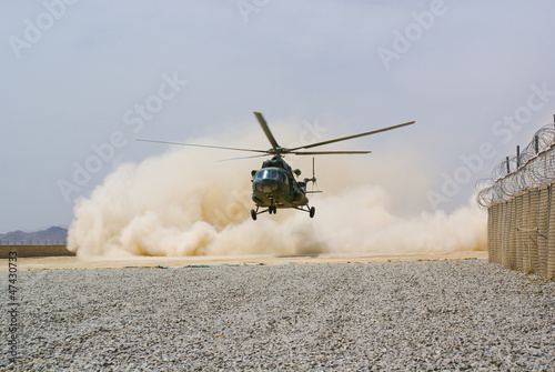 Tuinposter Helicopter helicopter landing in cloud of dust on desert