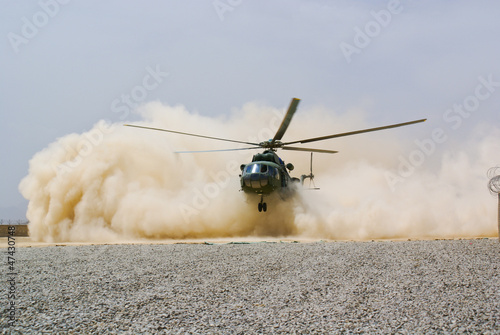 Poster Helicopter helicopter landing in cloud of dust of desert