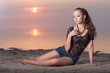 Sexy beautiful woman in jeans short on the beach at sunset